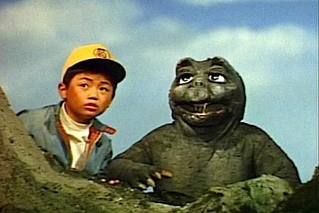 Tiga fase kehidupan Godzilla!: Sejak kecil, Godzilla sudah akrab dengan anak-anak. Lihat aja tuh lagi main petak umpet bareng sama si Takesi.